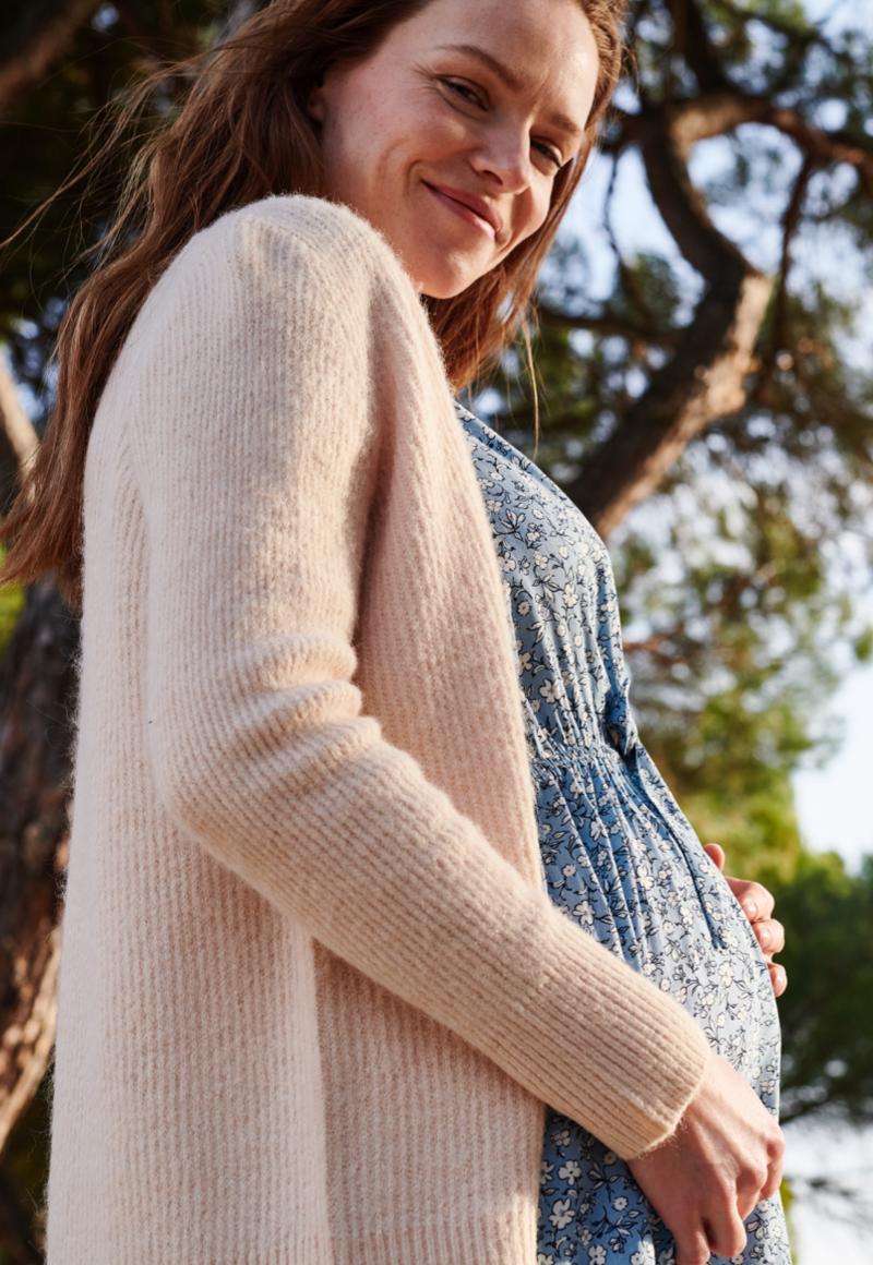 Un joyeux bébé dans un body rose est assis sur le lit | Guide bébé