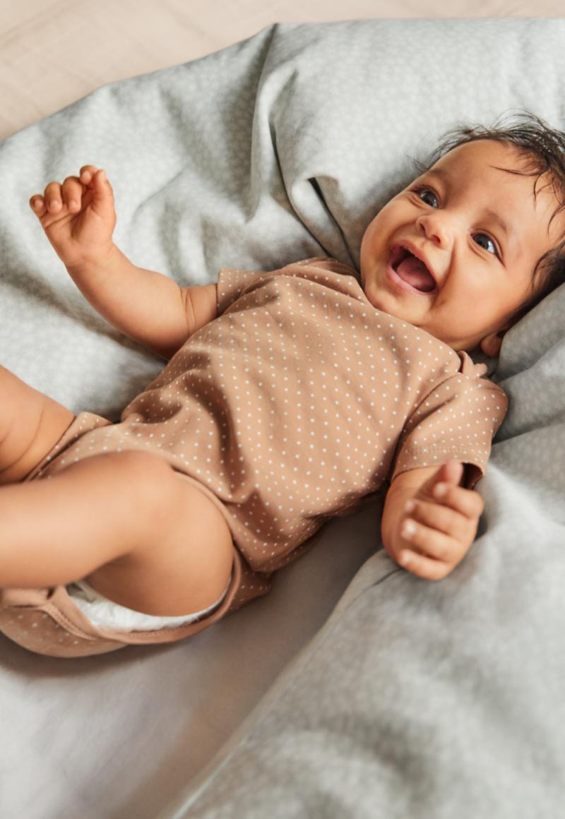 Un joyeux bébé dans un body bleu est dans un panier | Guide bébé