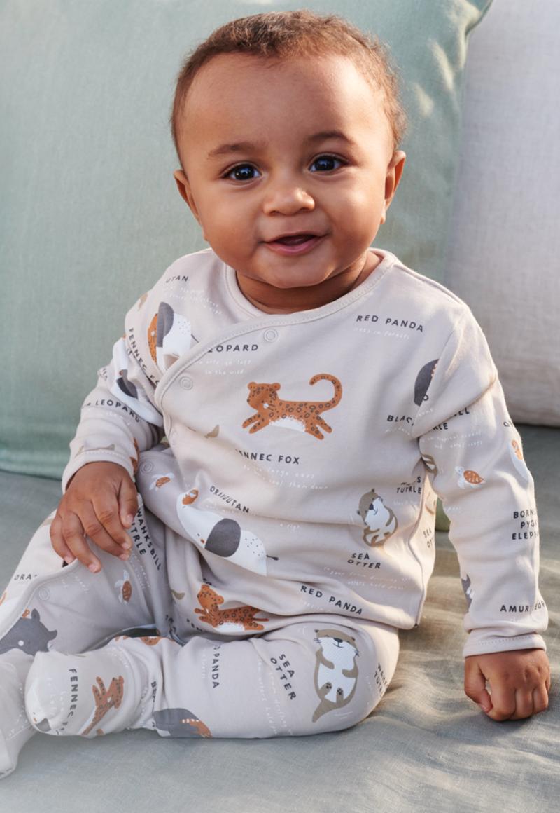 Un jeune enfant dans une tenue confortable composé d'un t-shirt et d'un pantalon, assis sur le lit