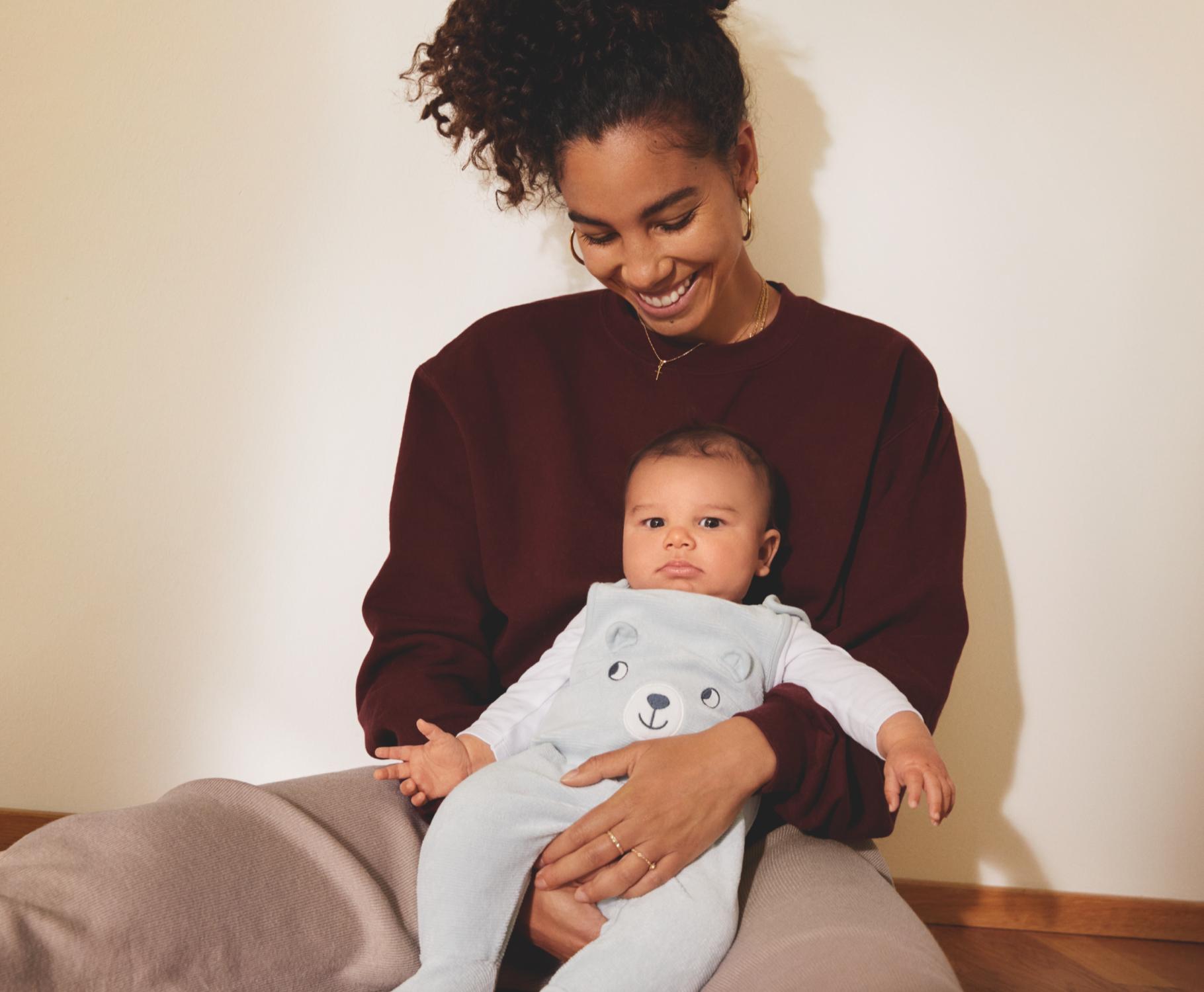 Un bébé baille sur son lit dans sa gigoteuse imprimée