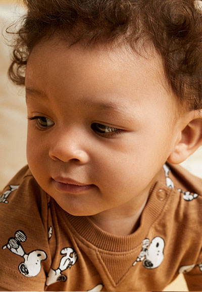 Un bébé en pyjama qui regarde sur le côté