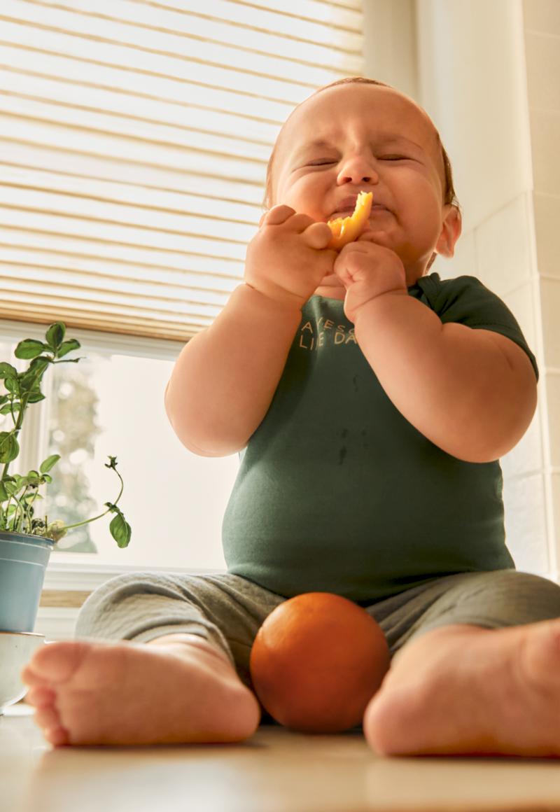 Les premiers jours avec bébé - Un bébé assis sur le lit dans ses beaux vêtements pour bébé