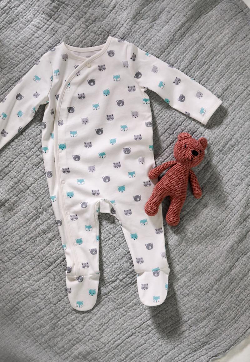 Baby in weißem C&A Babyschlafanzug sitzt auf Lammfell
