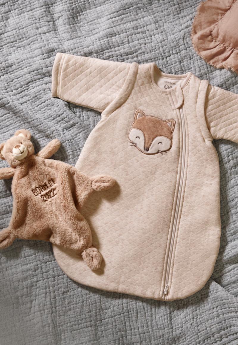 Baby in rosa C&A Babyschlafsack sitzt auf Bett