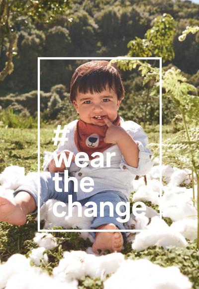 Un jeune enfant dans un pré qui porte des vêtements pour bébé de haute qualité en coton durable