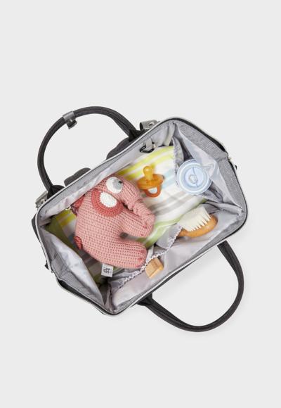 Schwangere Frau trägt eine gepackte Kliniktasche